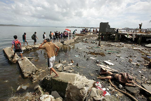 DEAD BODIES EVERYWHERE. Villagers walk past a dead body laying on damaged breakwater in Tacloban city. Photo by EPA/Francis Malasig