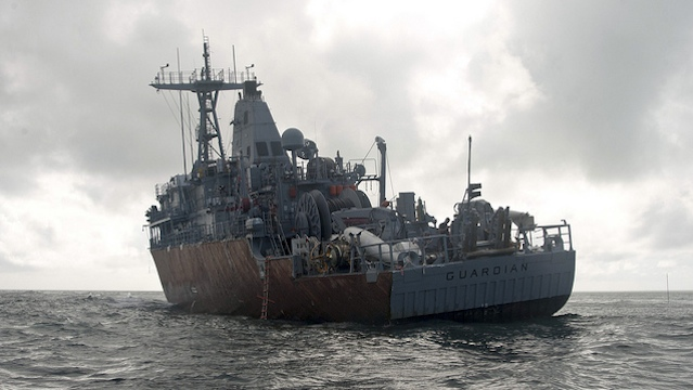 SITTING ON THE REEF. Led by US Navy Supervisor of Salvage Capt Mark Matthews, an experienced team of salvage professionals are ready to dismantle the 23-year-old minesweeper and safely remove the ship from the reef. February 8 photo courtesy of US Navy