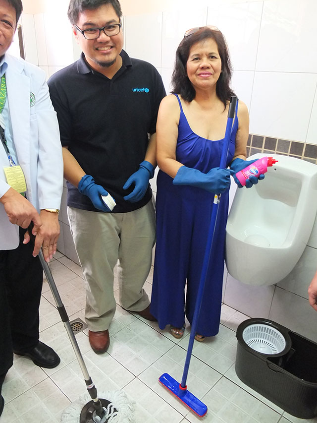 COMMON EFFORT. UNICEF's Dr. Mike Gnilo and PPHA's Dr.MaluhOrezca lend their hands at toilet-cleaning. Photo by Pia Ranada