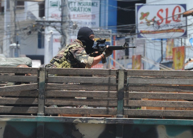TAKING AIM. A soldier on board a truck aims his weapon towards rebel positions as the stand-off between the two sides enters its sixth day in Zamboanga on September 14, 2013. AFP/Ted Aljibe