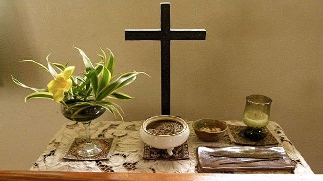 A TYPICAL ZEN ALTAR has flower arrangements, a cross, a Buddha statuette (not in picture), an incense pot, a candle and a kyosaku* stick
