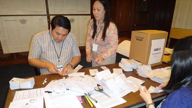 MANUAL COUNT. Deputy Consul General Tess de Vega (in blue) helps prepare the ballots for counting at the Philippine Consulate. All photos by Christina D.C. Pastor