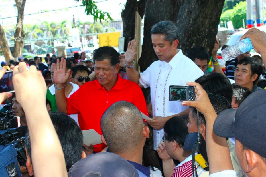 WINNER. Homer Saquilayan (left) takes his oath as Imus mayor before Cavite Gov. Jonvic Remulla outside city hall, where his unseated rival is still holed up. Photo by Mark Libanan
