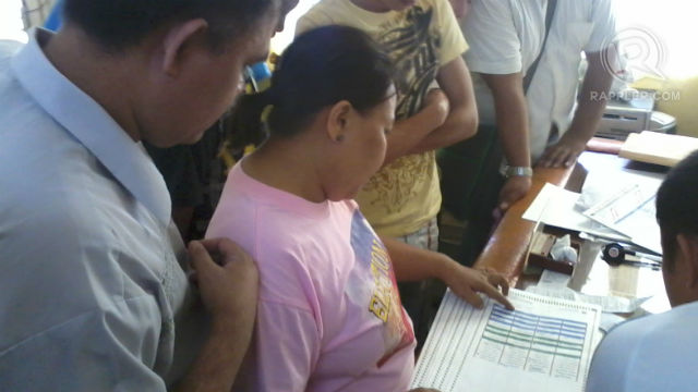 PREPPING UP. Tagbilaran Comelec chief Atty. Jonas Biliran (left) and poll watchers review the list of voters in Manansa Elementary School.