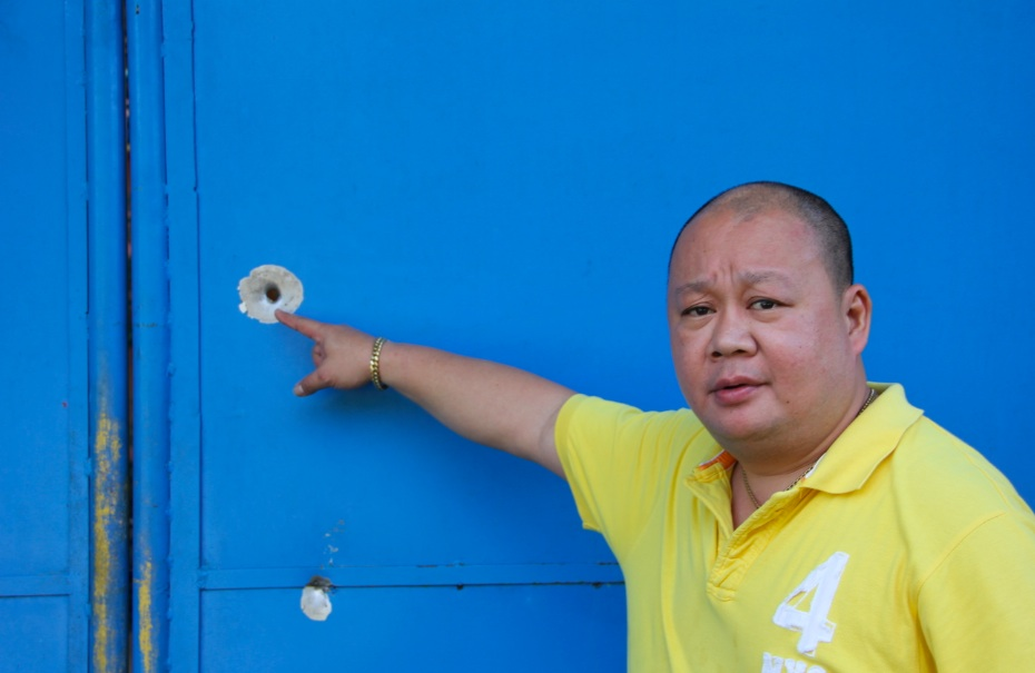 STRAFED. Comelec official Wilfred Jay Balisado shows the bullet holes on his gate in Dipolog City. Photo by Gualberto Laput