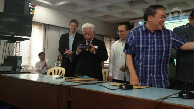 FOR GOOD LUCK? Comelec chair Sixto Brillantes Jr blows the sealed box containing the PCOS source code. Photo by Paterno Esmaquel II
