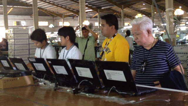 WAREHOUSE TOUR. Comelec chair Sixto Brillantes Jr (right) tours reporters in the Comelec warehouse in Cabuyao. Photo by Paterno Esmaquel II