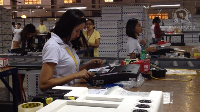 PCOS ASSEMBLY. A Comelec employee helps assemble ballot-counting machines in Cabuyao, Laguna. Photo by Rappler/Paterno Esmaquel II