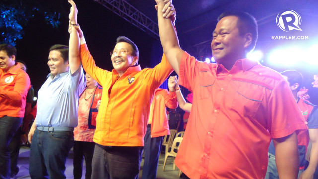 A FATHER'S HAPPINESS. Former President Joseph Estrada flashes a megawatt smile as he raises the hands of his sons, Sen. Jinggoy Estrada and senatorial candidate JV Ejercito. Rappler/Jerald Uy