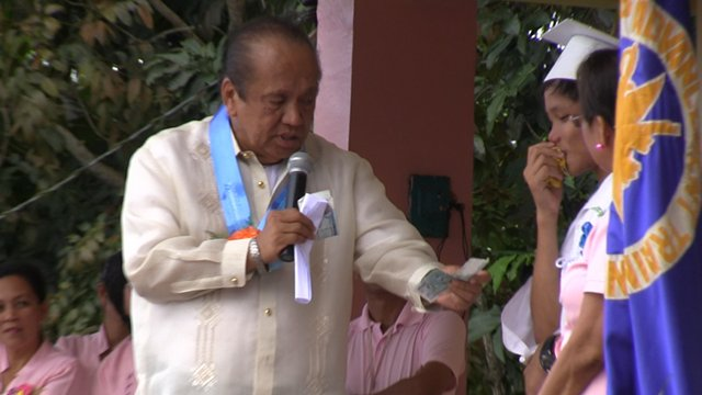 A GIFT. Third District Rep Luis Villafuerte Sr, who is running for Camarines Sur governor in May, gives a student P6,000 in cash to fund the graduates' transportation to his resort. Photo by RAPPLER