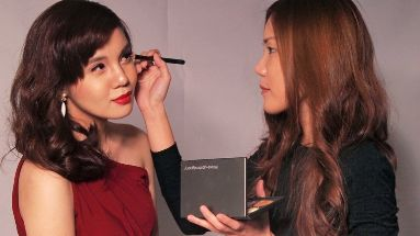 Pam retouches her model's make-up in a photo shoot,