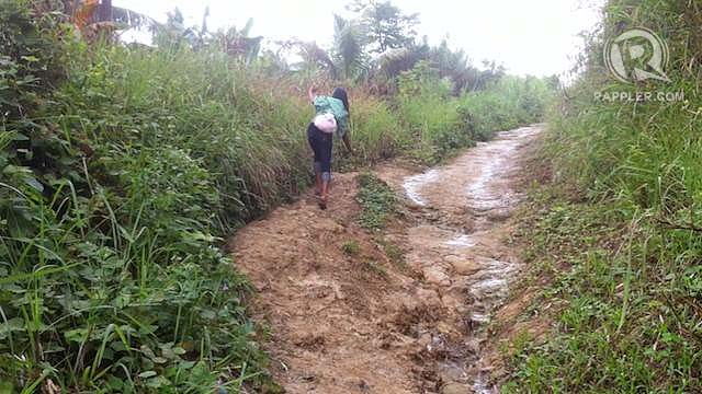 UNFINISHED ROAD. A lady tries to maintain her balance as she walks along an uneven road to a remote coastal barangay in Catbalogan, Samar. Photo by Judith Balea