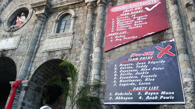 DEFYING COMELEC. The Bacolod Diocese cuts its oversized poster into half. Photo by Charlie Saceda